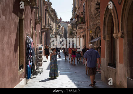 Tourists in street scene in the city of Taormina, East Sicily, Italy - Stock Image