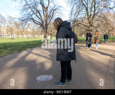 Woman taking picture of one of 90 plaques in ground, on The Diana Princess of Wales Memorial Walk - this one in - Stock Image