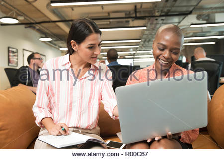 Businesswomen using laptop on sofa - Stock Image