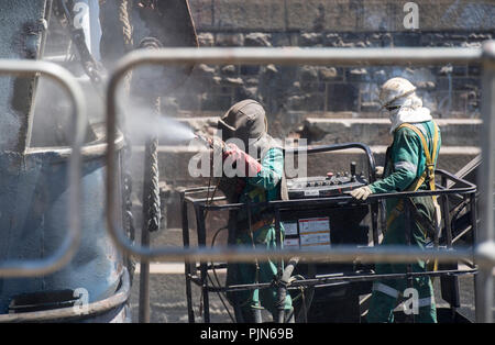 Shipyard employees working on a large vessel docked in Cape Town, South Africa - Stock Image