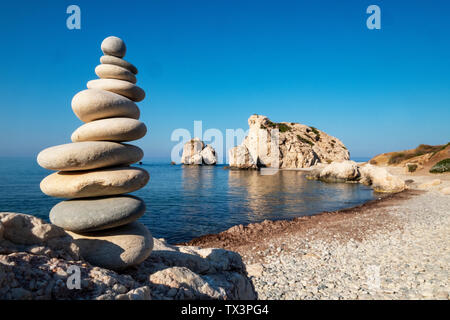 A stone stack in front of  Aphrodite's Rock (Petra Tou Romiou), Paphos region, Republic of Cyprus. - Stock Image