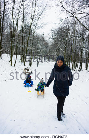 Poznan, Poland - January 26, 2019: Woman pulling a sled with toddler on a footpath with snow at a park on a cold winter day. - Stock Image