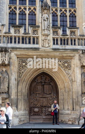 Man stood in the carved doorway of Bath Abbey using his mobile phone with passers by - Stock Image
