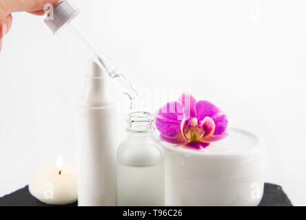Woman hand take liquid collagen or hyaluronic acid with pipette from glass bottle, cream jars on the background, selective focus on dropper and liquid - Stock Image
