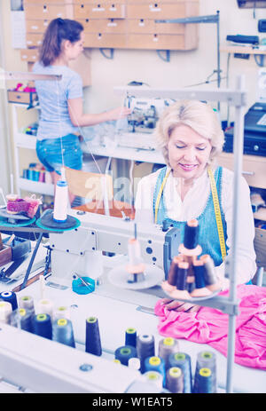 Portrait of two professional skilled female tailors working at a sewing workshop - Stock Image
