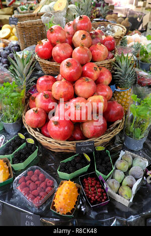 Pomegranates and various fruits on a Borough Market stall in autumn November South London England UK   KATHY DEWITT - Stock Image
