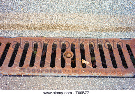 Poznan, Poland - October 31, 2018: Metal rain drain by a sidewalk in the city. - Stock Image