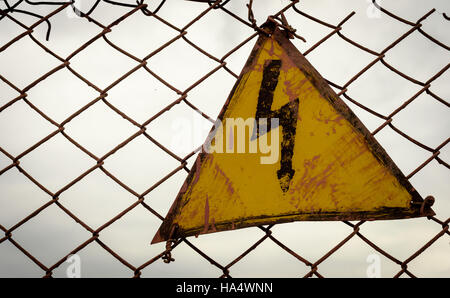 Lightning bolt electricity warning sign in a yellow triangle set against a dark sky wire mesh background - Stock Image