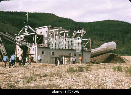 Floating Gold Dredge; Dawson City, Yukon Territory, Canada.  Dredge scoops up river rock and gravels, separating - Stock Image