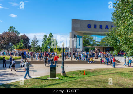 Crowd of people walking, enjoying a sunny day in front of the Gerald R. Ford Presidential Library and Museum in Grand Rapids, Michigan. - Stock Image