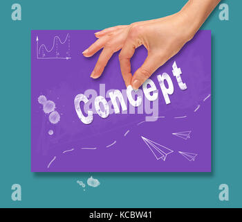 A hand picking up a concept on a colorful drawing board. - Stock Image