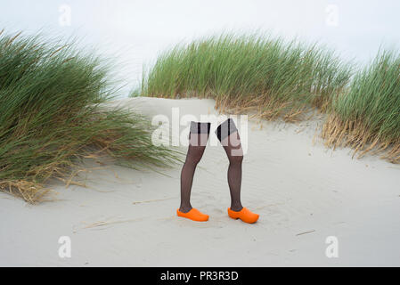 Stockings and wooden shoes (legs). Dunes in the Netherlands. - Stock Image