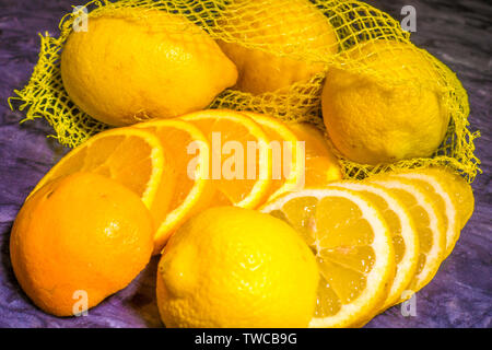 A batch of bright yellow fresh lemons, with two of them sliced, on a granite chopping board. - Stock Image