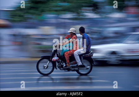 Young lady driving a motor bike in Saigon Vietnam with child in front and husband behind in heavy traffic in the - Stock Image