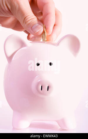 Stock image of man depositing a coin in a piggy bank - Stock Image