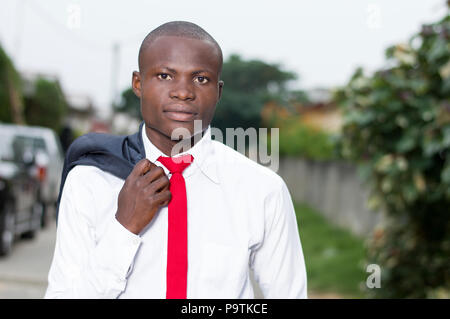 Portrait of young African businessman with his jacket on his shoulder. - Stock Image