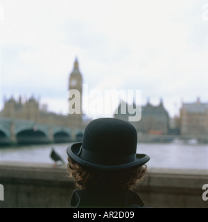 A man in a bowler hat and bird sitting watching the River Thames, Big Ben and Houses of Parliament, Westminster in  London UK  KATHY DEWITT - Stock Image