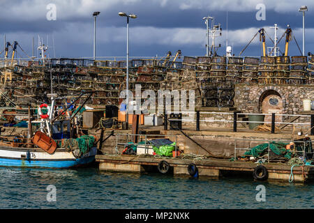 Lobster pots piled up beside the harbour at Brixham, Devon, UK. 2018. - Stock Image