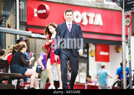 Young white English businessman walks through a busy city centre with the general public in the background and near the shopping - Stock Image