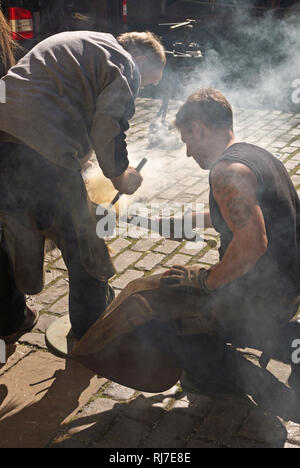 Two blacksmiths at work shoeing a horse, Beamish Museum, County Durham, UK - Stock Image