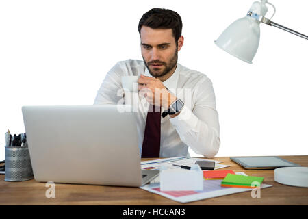 Businessman working on laptop in office while having coffee - Stock Image