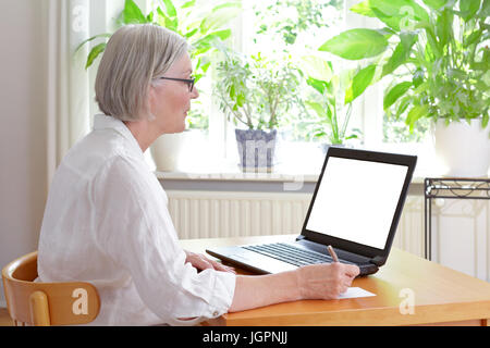 Senior woman at home in front of her laptop taking notes, online advice or e-learning concept template, white screen, - Stock Image