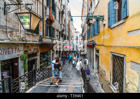 Tourists shop for souvenirs, sightsee and dine on a narrow alley in the historical center of Venice, Italy. - Stock Image