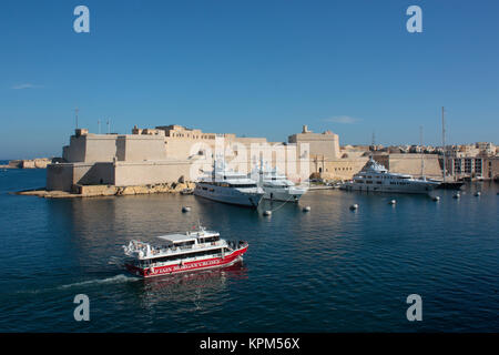 Grand Harbour tour boat passing by Fort St Angelo, Malta, with tourists sightseeing on board. Tourism is an important - Stock Image