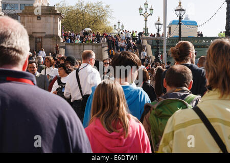 Crowds of tourists mixed with commuters on London South bank at Westminster bridge. - Stock Image