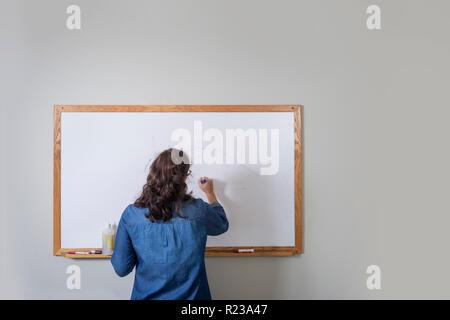 Woman Writing On White Board, USA - Stock Image