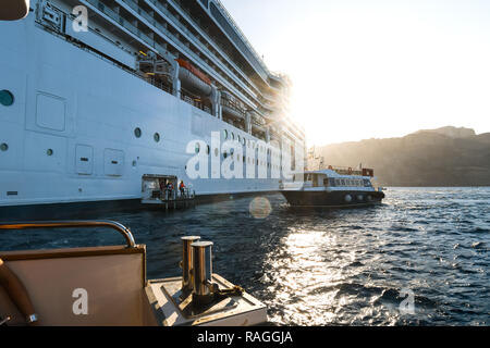 A tender boat pulls away from a large cruise ship as another docks, as the sun rises inside the caldera, the Aegean Sea at Santorini, Greece - Stock Image