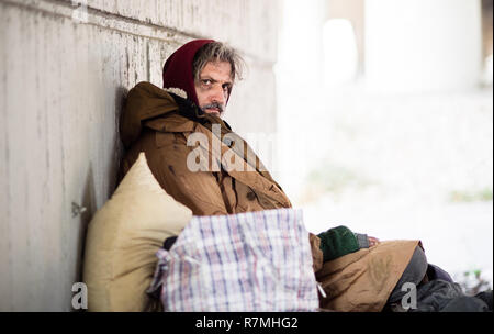 A side view of serious homeless beggar man sitting outdoors, leaning against a wall. Copy space. - Stock Image