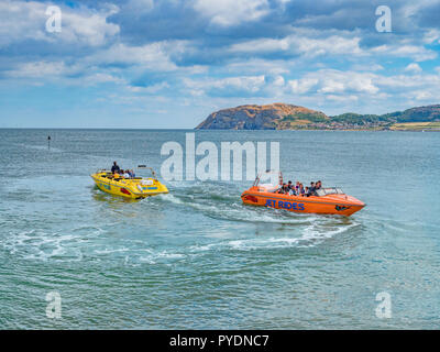 15 July 2018: Llandudno, Conwy, UK - Jet boat rides in the bay, with the Little Orme in the background. - Stock Image