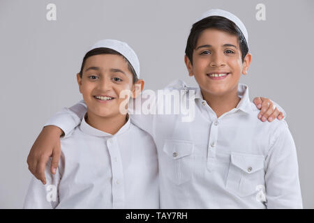 Young Muslim boys with caps smiling and holding each other - Stock Image
