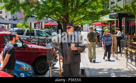ASHEVILLE, NC, USA-10 JUNE 18: Friends conversing, and tourists and residents enjoying a summer Sunday on Page Ave. - Stock Image