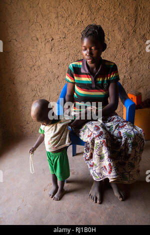 Samba village, Yako Province, Burkina Faso: Abzetta Sondo, 19, and her child Noel Nougtara, 15 months. Her baby is suffering from acute malnutrition. - Stock Image