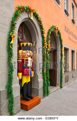 A life-size toy soldier watches passersby from doorway in Käthe Wohlfahrt's Weinachtsdorf, Rothenburg ob - Stock Image