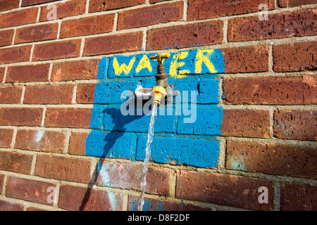 Running water from an external tap which had been left on. - Stock Image