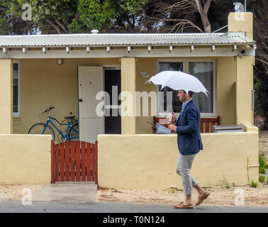 Caucasian man with a white umbrella and wearing blue jacket walking past a cottage on Rottnest Island WA Australia. - Stock Image