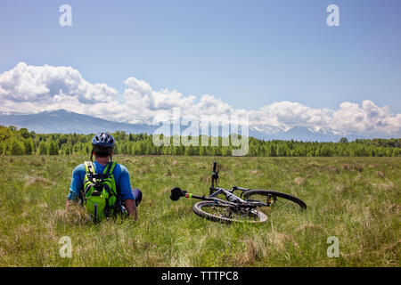 Rear view of cyclist sitting on grassy field against cloudy sky - Stock Image