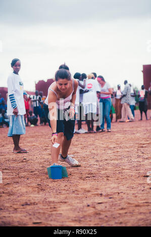 Mali, Africa - Young caucasian woman stretching with black african children, boys and adults to play soccer in a rubbish dump. Rural area near Bamako - Stock Image