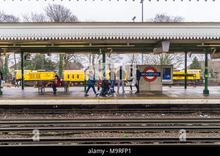 Passengers on the platform in front of a Schweerbau rail milling train parked in a siding at Woodford Underground station, Essex, England - Stock Image