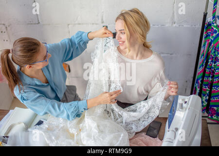 Talanted female clothing designer is selecting a suitable fabric for a party dress, alternately bringing lace cuts of fabric to the client's body - Stock Image