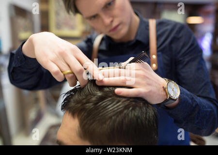 male hairdresser cutting hair at barbershop - Stock Image