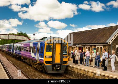UK, Yorkshire, Settle, passengers on Railway Station platform waiting for Settle to Carlisle Railway Line train in sunshine - Stock Image