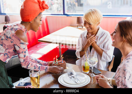 Young woman serving birthday cake to friend in restaurant - Stock Image