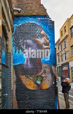 LONDON ENGLAND BRICK LANE PERSON PHOTOGRAPHING  WALL PAINTINGS OR GRAFFITI - Stock Image