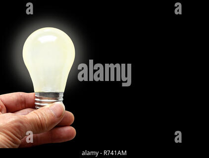 Man holding illuminated bulb with bare hands against black background with copy space. Concept of bright idea, innovation, imagination, inspiration, v - Stock Image