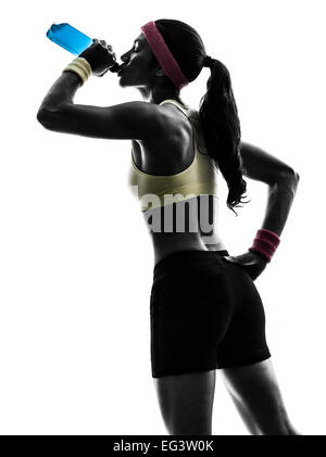 one woman exercising fitness drinking energy drink in silhouette on white background - Stock Image