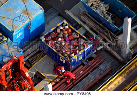 Workers by container of lids on offshore oil platform - Stock Image